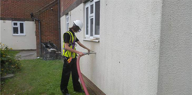 Wall being injected with insulation material